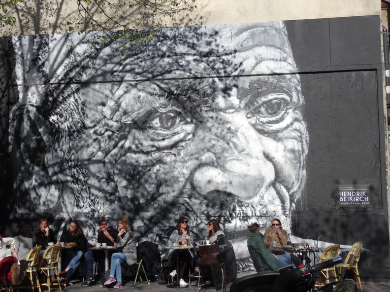 People relax in front of street art on the rue Oberkampf, Paris