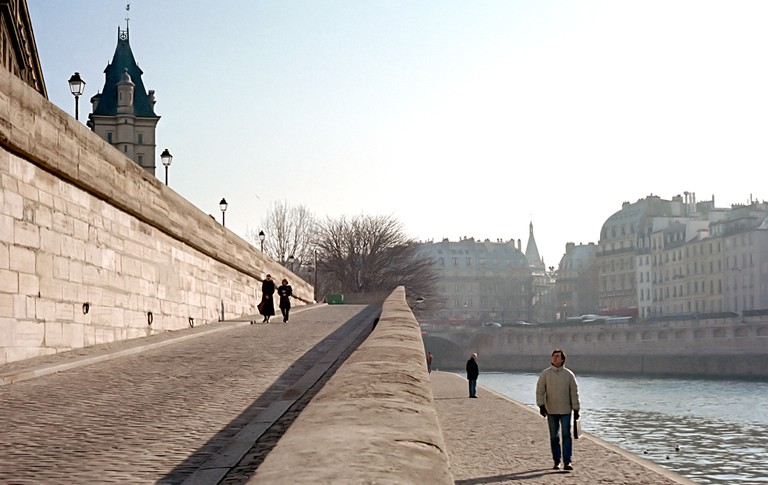People taking a late afternoon stroll on the banks of the Seine river in Paris.