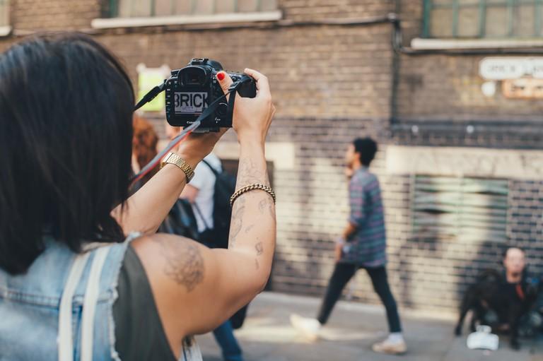 Tourists photographing graffiti on Brick Lane, London