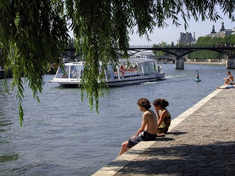 Young couple sit in the sun on island park of le Vert Galant, Paris