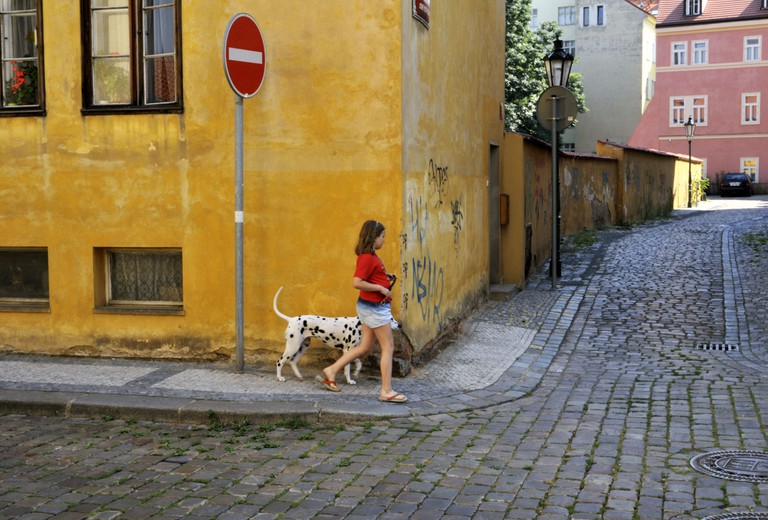 A girl walking the dog in the Jewish Quarter of Prague, Czech Republic.