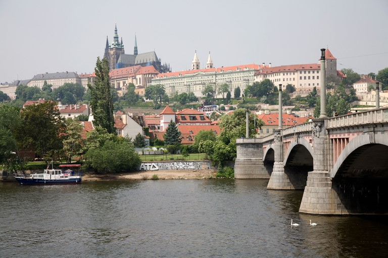 The river Vltava flowing under Manesuv Most with Prague Castle Prazsky Hrad in the distance in Prague Czech Republic