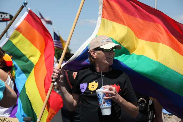 Same-sex supporter holding rainbow flag at Gay Pride March in Albuquerque, New Mexico
