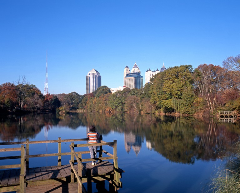 Woman looking across Piedmont Lake, Piedmont Park, Atlanta, Georgia, USA.