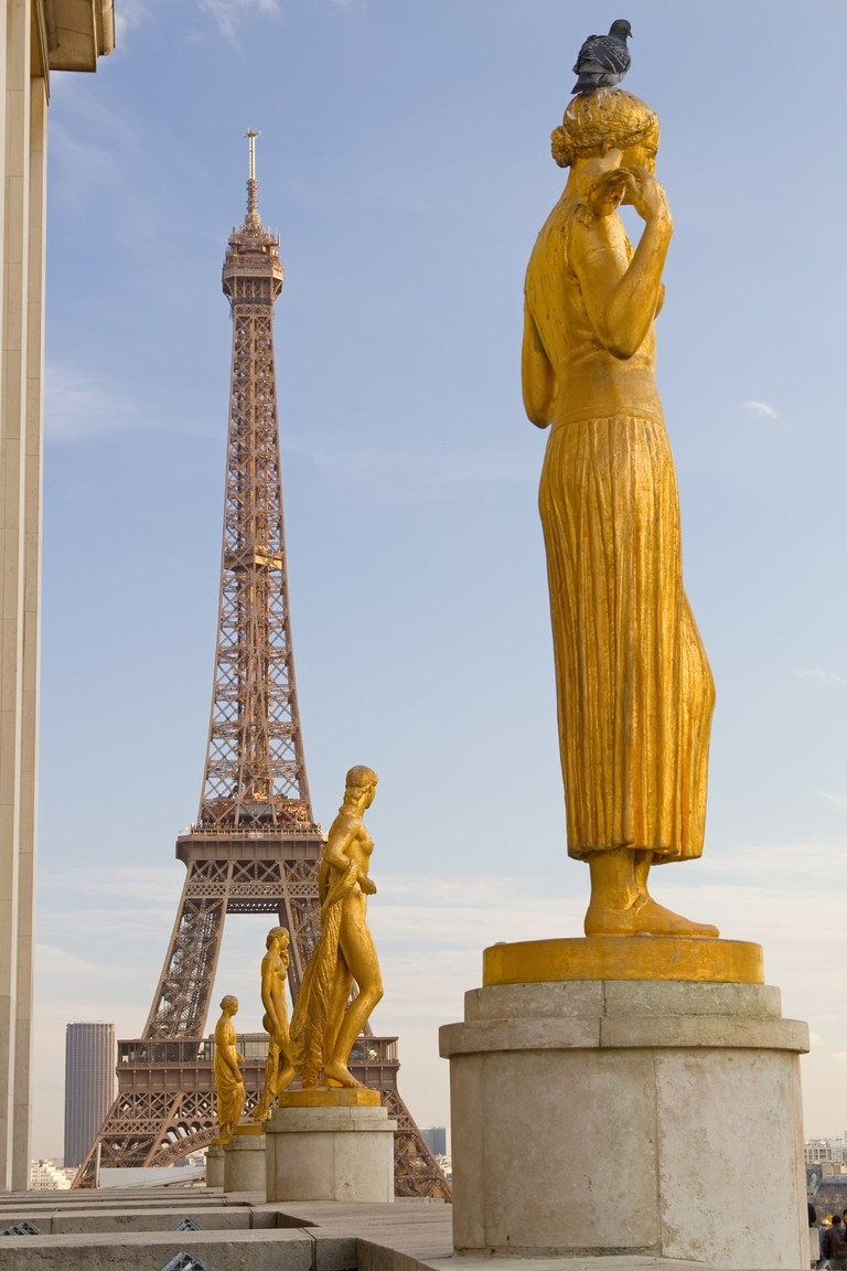 The famous landmark of Paris, Eiffel Tower, as seen behind some statues of Palais de Chaillot