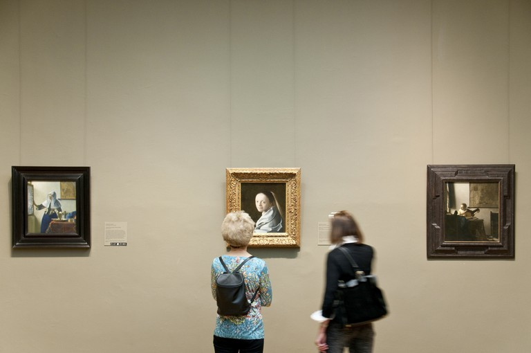 Museum visitors looking at Study of a Young Woman, ca 1665-67, by Johannes Vermeer, Metropolitan Museum of Art, New York City.