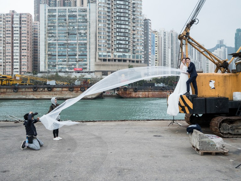 "A couple pose for a wedding photoshoot on a crane at the ""Instagram Pier"", Hong Kong"