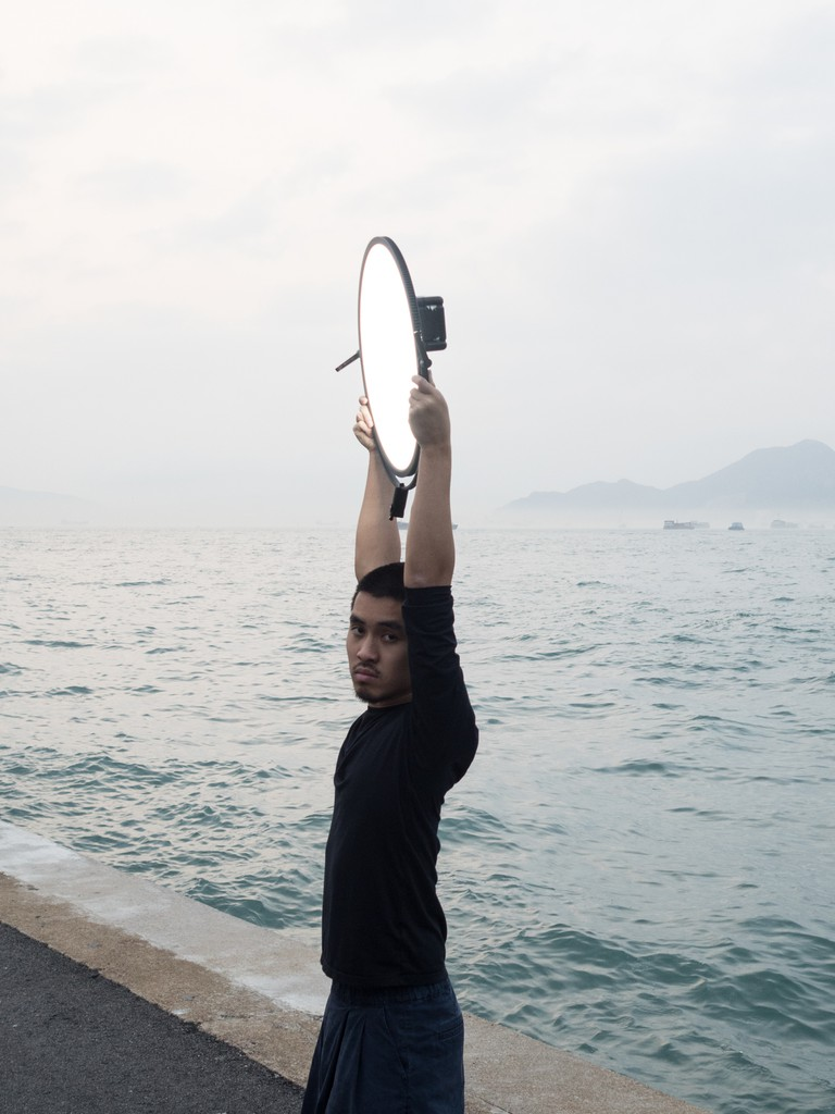 "A man posing with a reflector at the ""Instagram Pier"", Hong Kong"