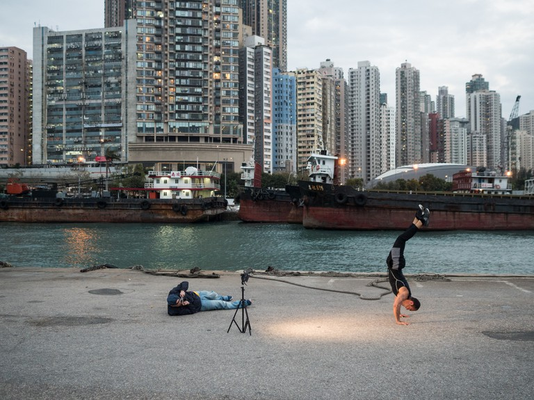 "A man is balancing on his hands for a photoshoot at the ""Instagram Pier"", Hong Kong"