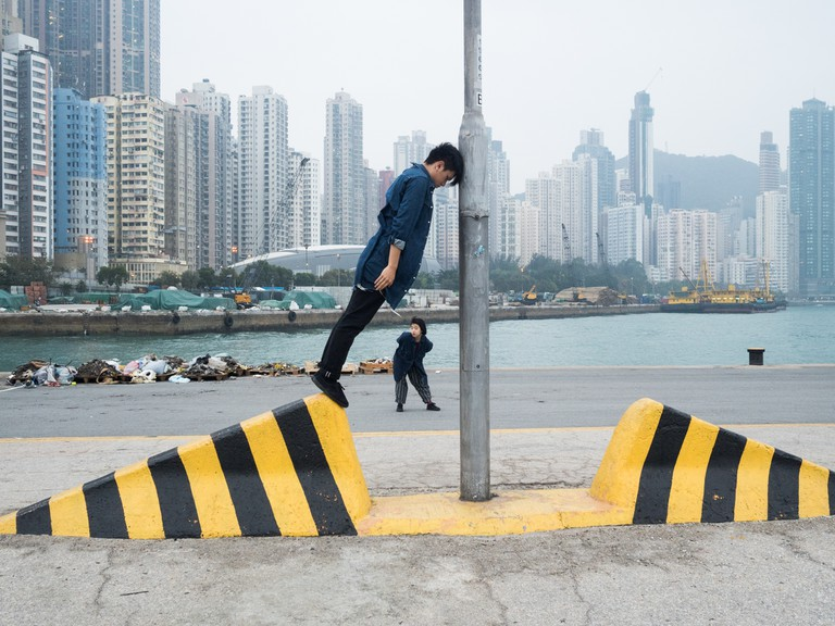 "A couple photographing themselves on a lamppost at the ""Instagram Pier"", Hong Kong"