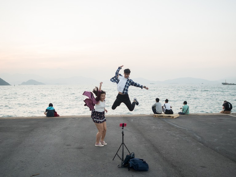 "A couple is jumping for a selfie at the ""Instagram Pier"", Hong Kong"