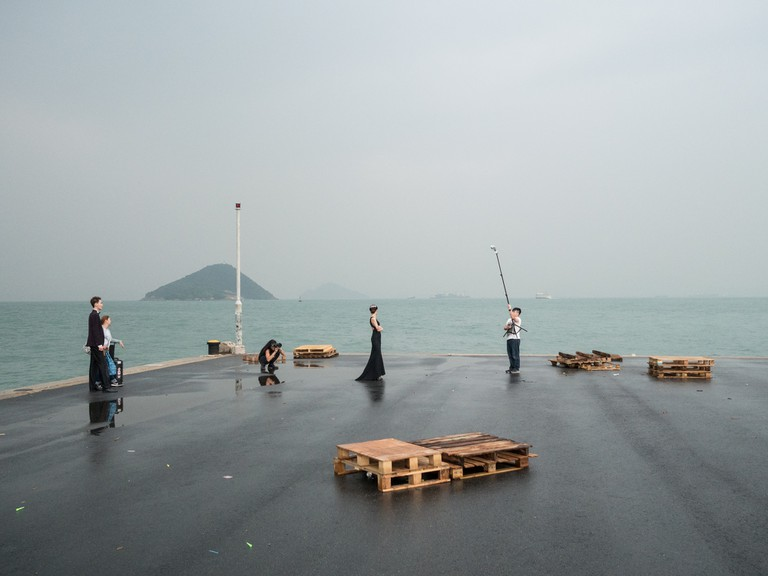 "A wedding photo shoot at the pier, in the background is Green island at the ""Instagram Pier"", Hong Kong"