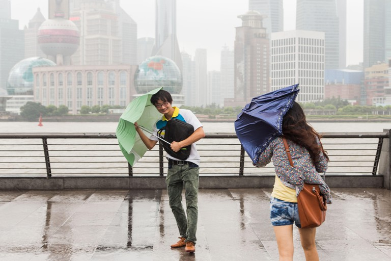 Visitors to the Bund take shelter from gusty winds as Typhoon Haikui made landfall in eastern China effecting life for 23-million people in the business hub of Shanghai on August 8, 2012 in Shanghai, China.