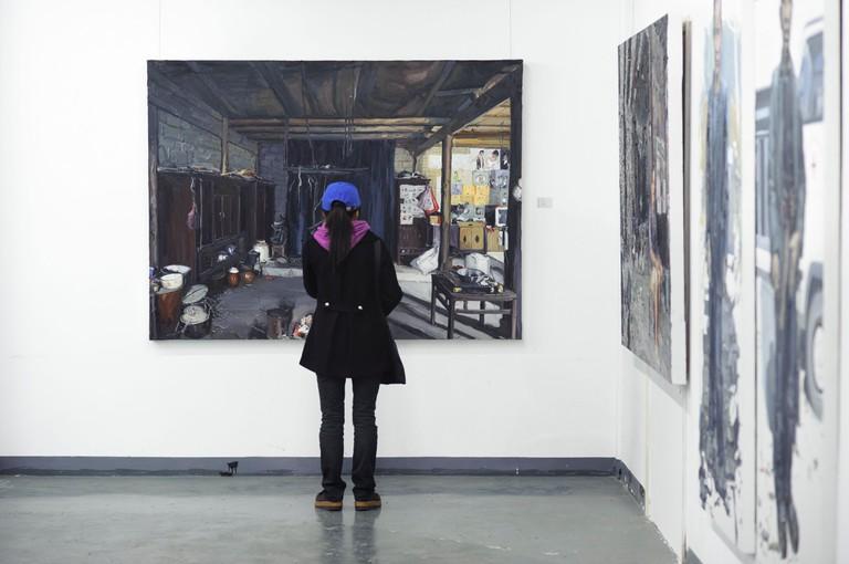 A girl studies a painting at Shanghai's 50 Moganshan Road art district, Shanghai, China
