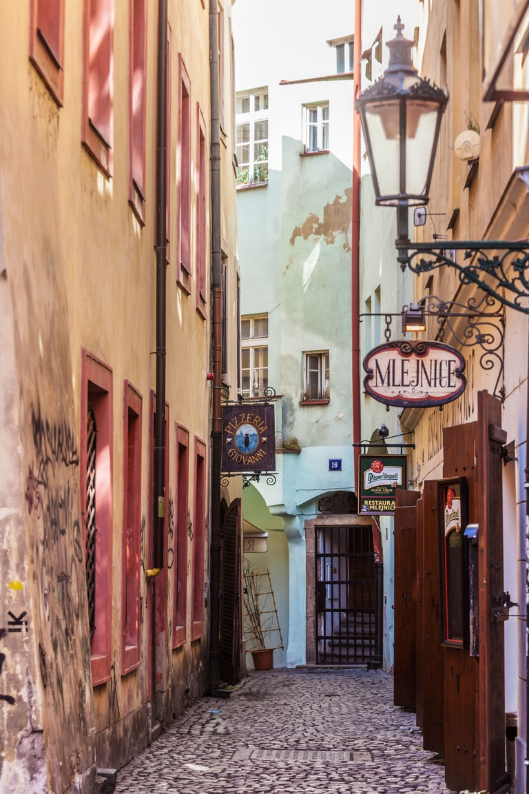 A small cobbled alleyway with bars and restaurants in the Old Town district of Prague