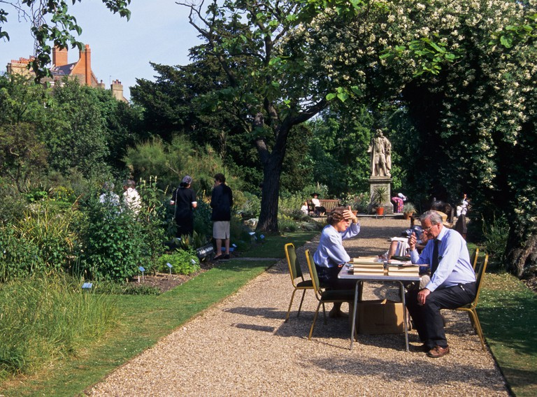 People relaxing at Chelsea Physic Garden, London, England.