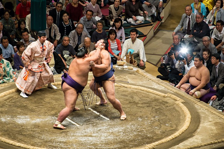 Sumo wrestlers fighting in the wrestling ring at the Ryogoku Kokugikan, Tokyo, Japan