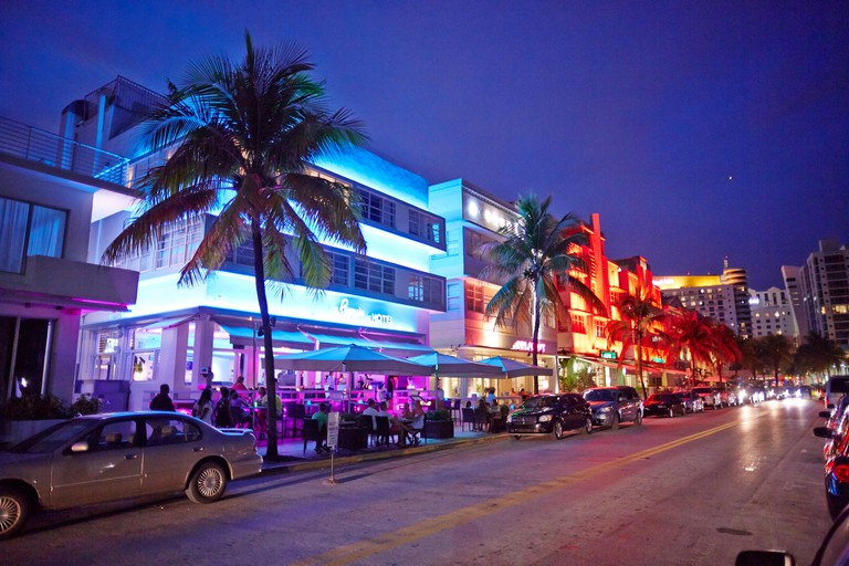 Bars and restaurants glow in the evening light on Ocean Drive in Miami, Florida.