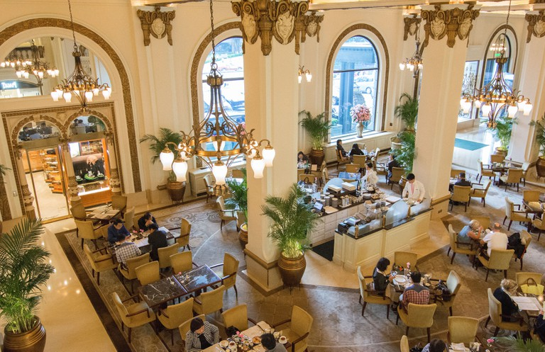 People enjoy high tea in the lobby of The Peninsula Hotel in Hong Kong