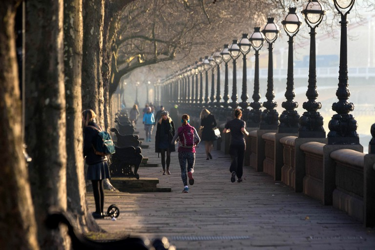 Runners jogs along the River Thames at Cheyne Walk as the sun rises on a chilly but clear London morning