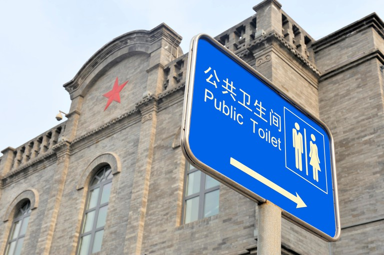 Sign in English and Chinese with text: Public Toilet.At background building with red cross
