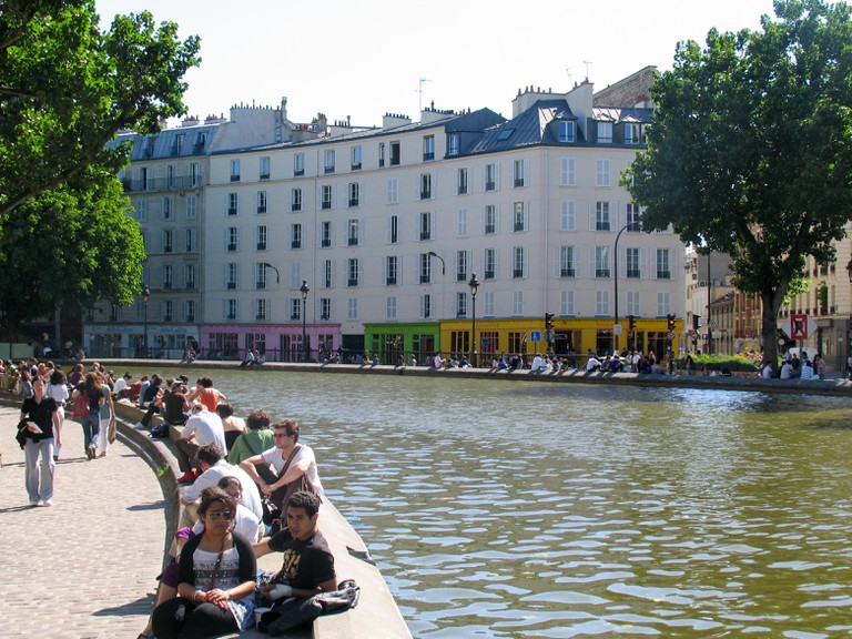 People sitting and enjoying the spring sun along Canal Saint-Martin, Paris.