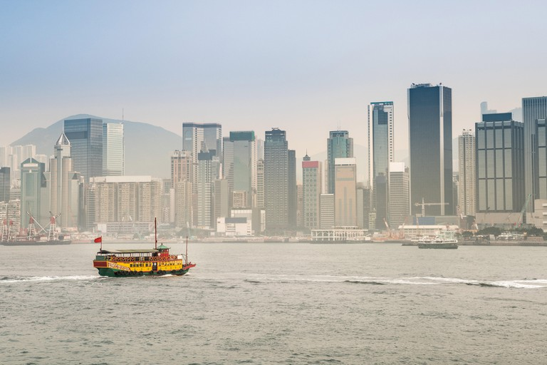 Panorama of a ferry in the Victoria Harbour with the skyscrapers and the Hong Kong skyline. China.