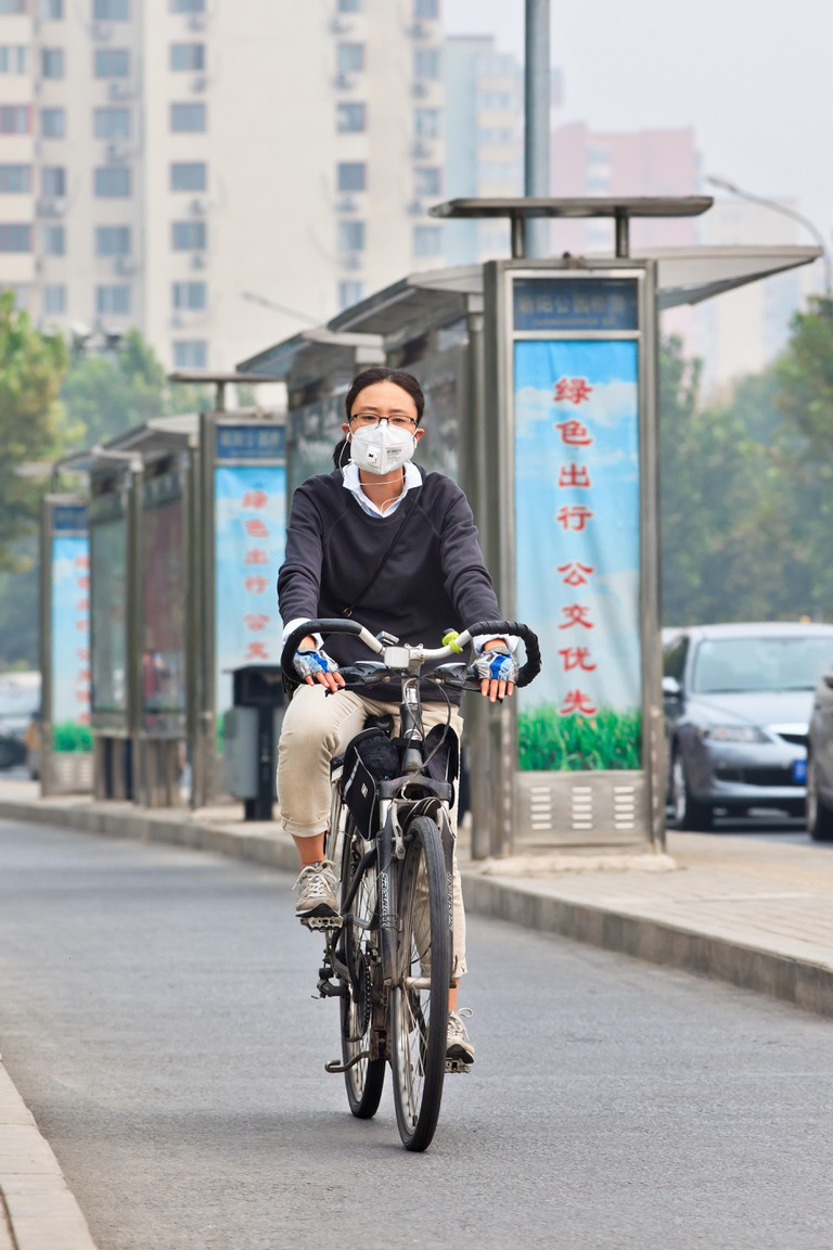 BEIJING-OCT. 19, 2014. Woman on a bicycle with face mask. Beijing raised its smog alert to orange because the air quality is a health threat. Face mas