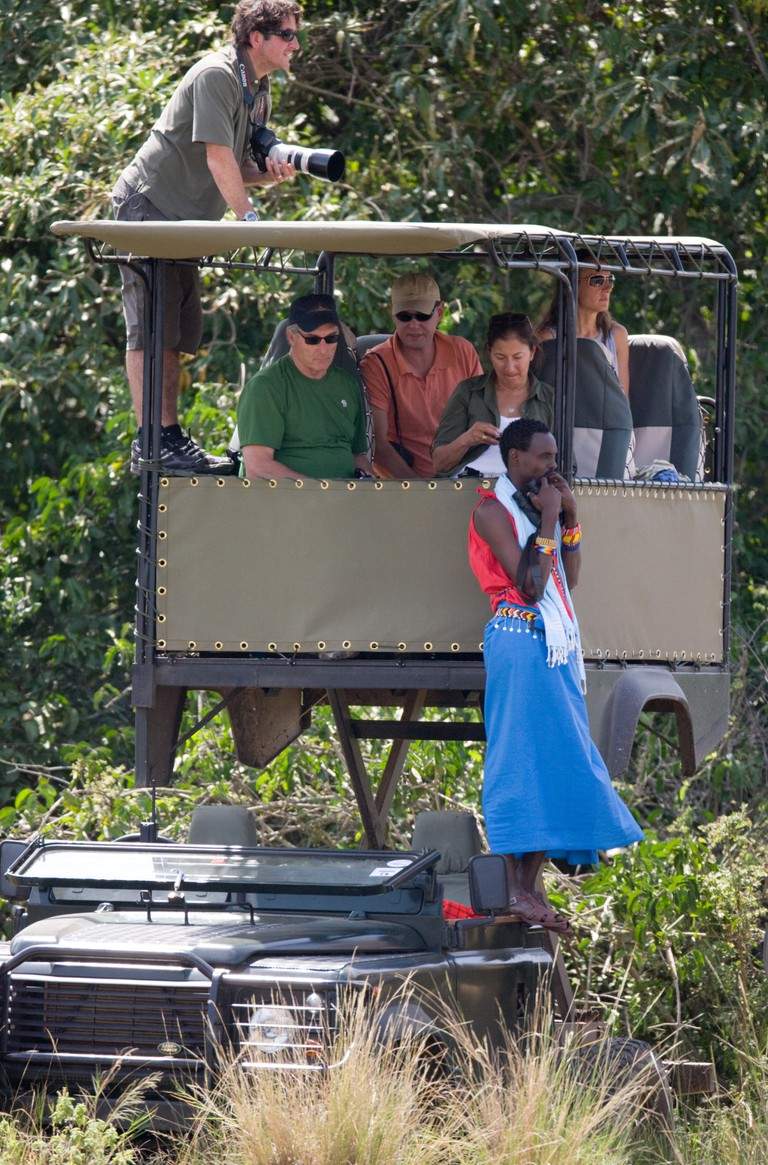 Tourists on a safari in a special vehicle watching an elephant in Masai Mara, Kenya.