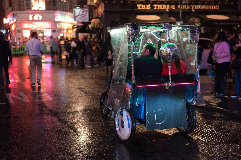 Views of a cycle tuktuk with neon lighting on Old Compton Street in Soho, London on a rainy night. From a series of photos taken on a rainy night in S