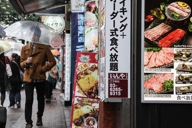 A man with an umbrella walks past street food in the Korean Town, Shin-okubo Station, Tokyo, Japan.