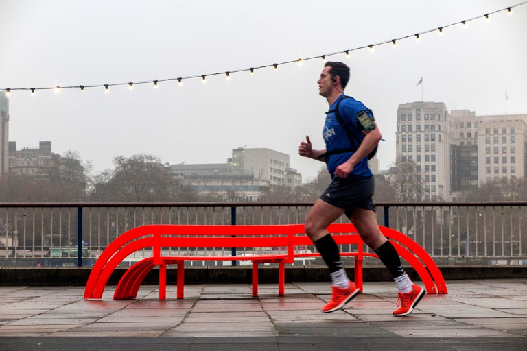A man runs along the South Bank in front of a Jeppe Hein orange bench -part of the Modified Social Bench project and a string of lights on a grey day