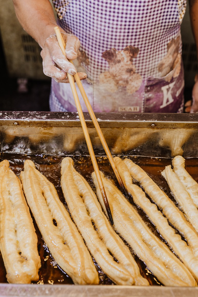 'You tiao' are fried in hot oil until puffy and golden