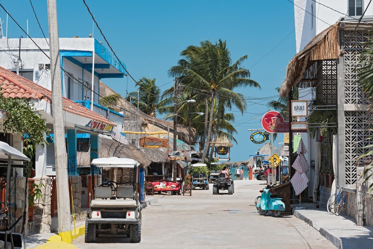 Sandy road with tourists and stalls on Holbox Island, Quintana Roo, Mexico located in north yucatan peninsula.