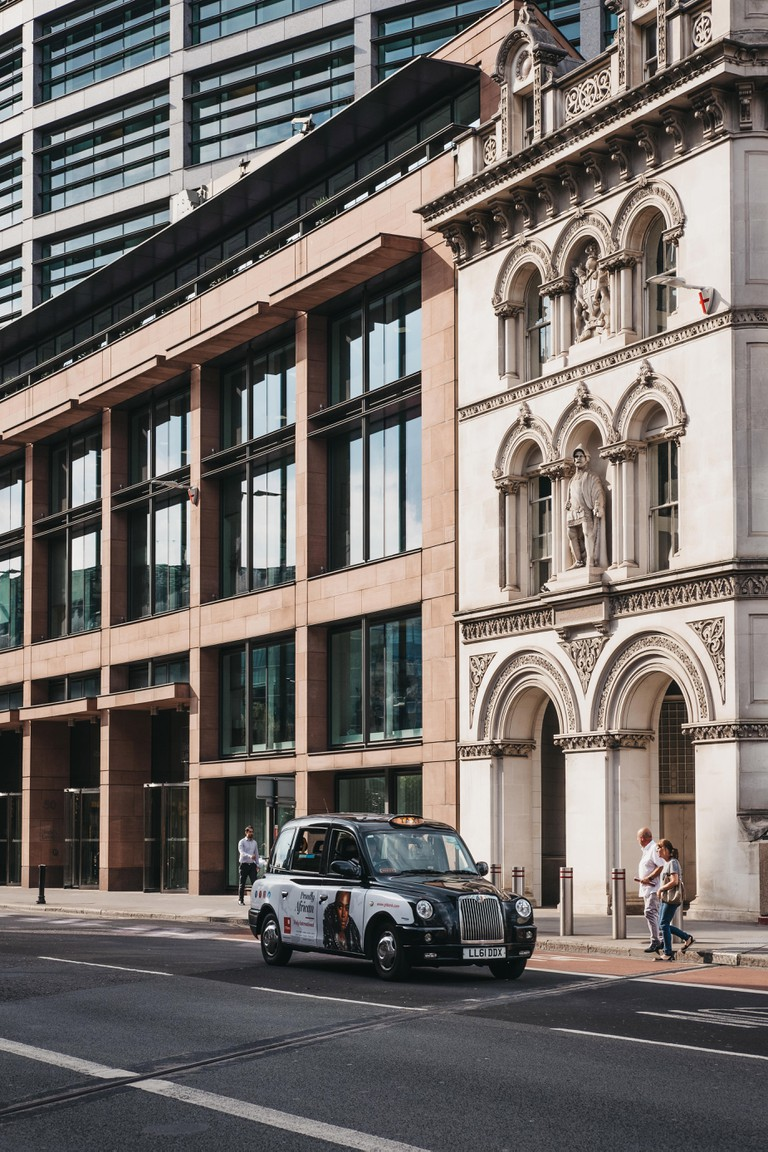London, UK - July 24, 2018: Black cab in front of a modern office building in the City of London, London's famous financial district.