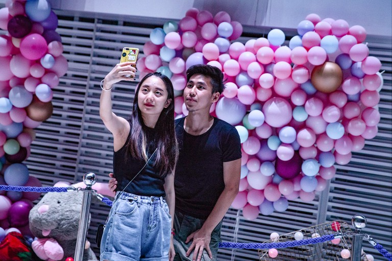 A Chinese couple poses for selfies next to a heart made by balloons during Qixi Festival or called Chinese Valentine's Day.