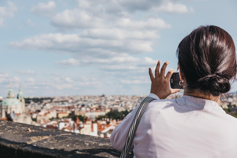 A solo female traveller taking photos from the viewing platform at Prague Castle