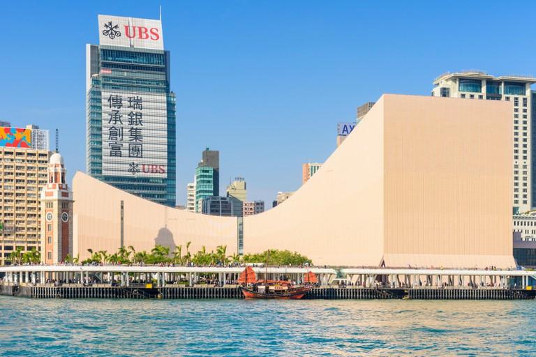 The Hong Kong Cultural Centre and clock tower overlook the Kowloon public pier and moored Dukling junk boat in Tsim Sha Tsui, Kowloon, Hong Kong