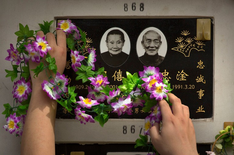 A well-wisher reaches to put a floral decoration on a columbarium at the Babaoshan Revolutionary Cemetery during the Qingming festival in Beijing.