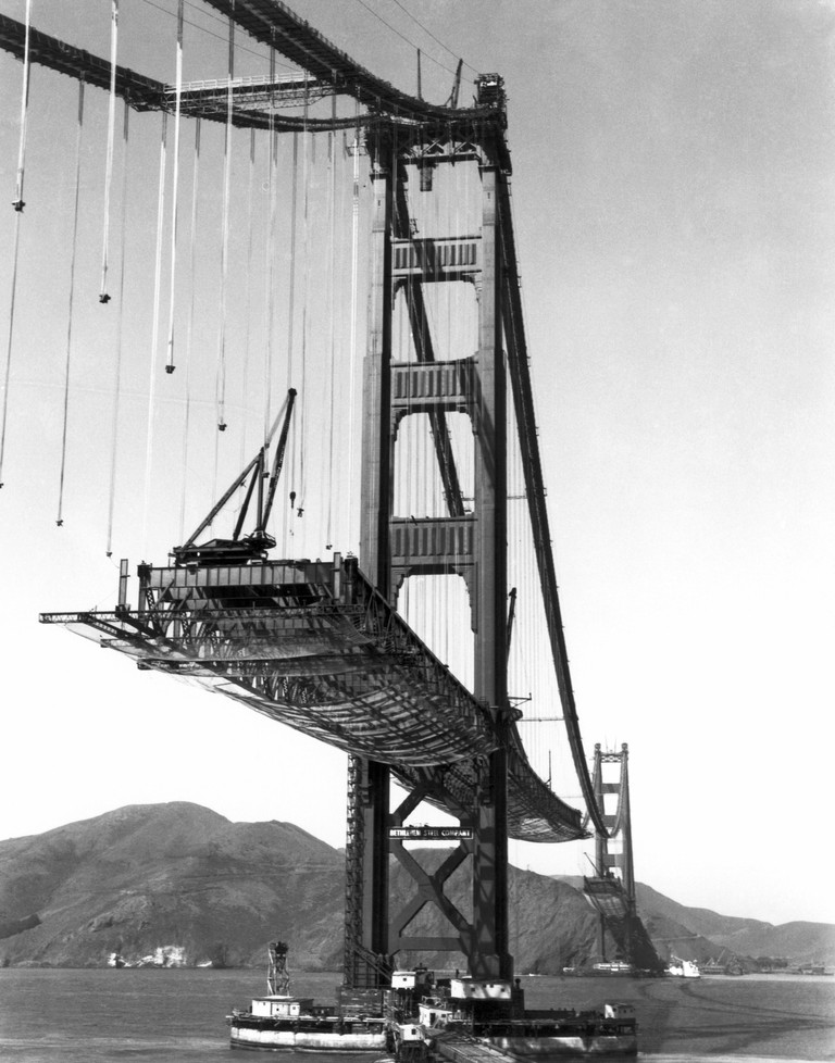 The Golden Gate Bridge under construction, with the roadbed being suspended from the cables.