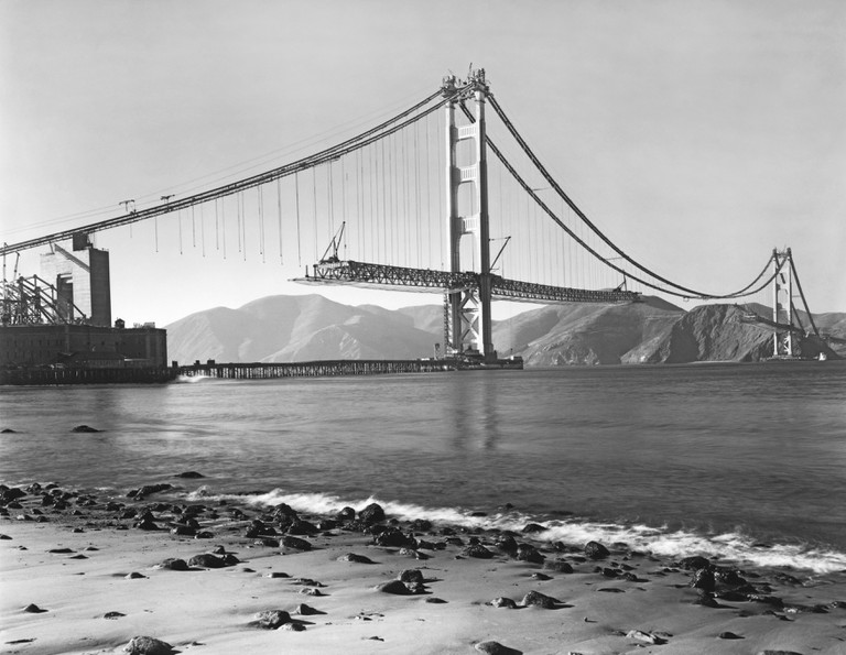 View from Crissy Field of the construction of the Golden Gate Bridge with the roadbed being installed.