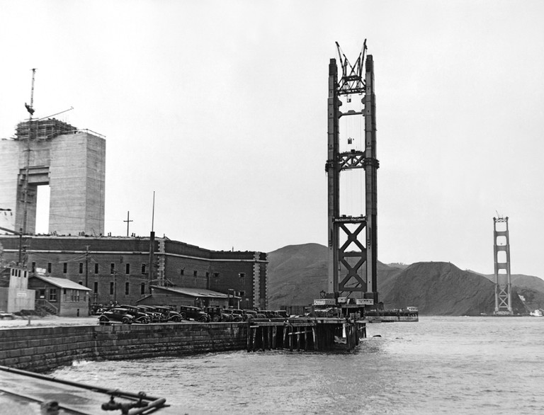 The Golden Gate Bridge under construction with the Pylon #1 and the North and South Towers rising above Fort Point.