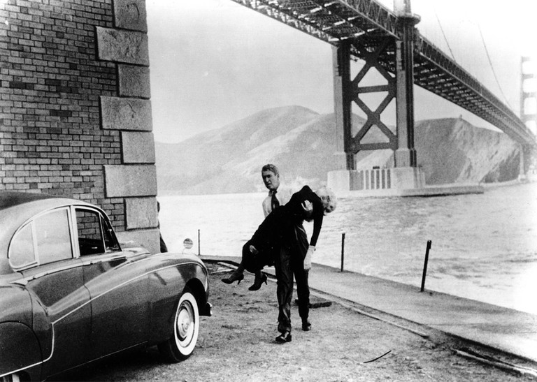 James Stewart and Kim Novak against the Golden Gate Bridge in the background in scene still from Alfred Hitchcock's Vertigo (1958).