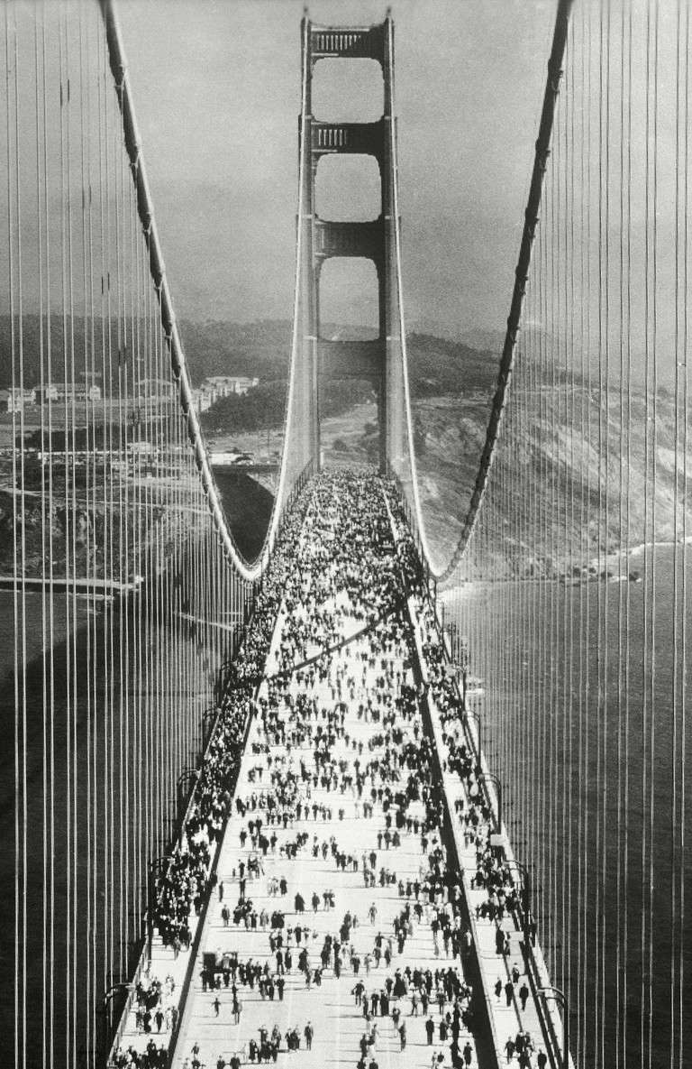 The Golden Gate Bridge, the longest suspension bridge in the world at the time was opened on May 27, 1937. A view taken from one of the towers of pedestrians swarming across the Golden Gate Bridge immediately after the opening.