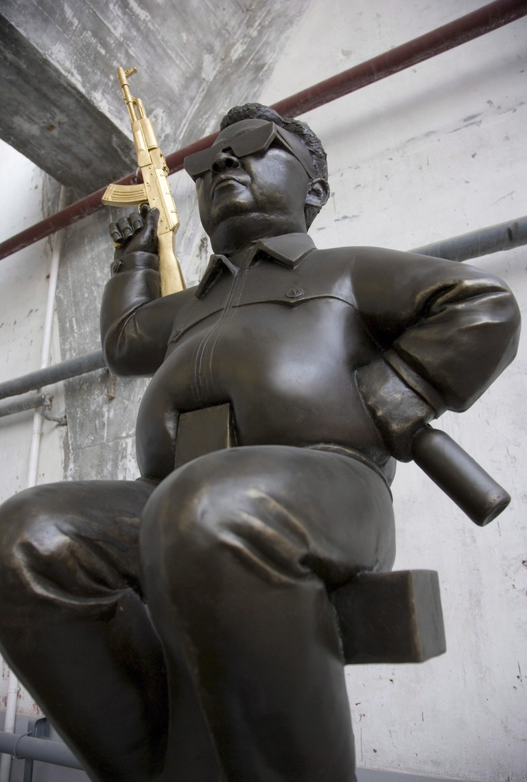 A Sculpture of North Korean Leader Kim Jong Il Wielding a Golden Ak47 Gun by Wang Zheng Titled 'The Sun of the Democracy Club'