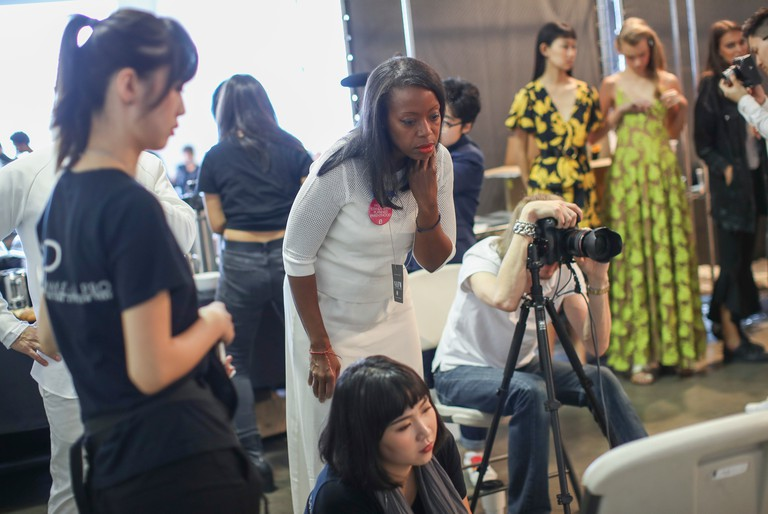 Designer Tracy Reese, center, inspects photographs of models backstage ahead of her Spring 2018 collection presentation during NYFW.