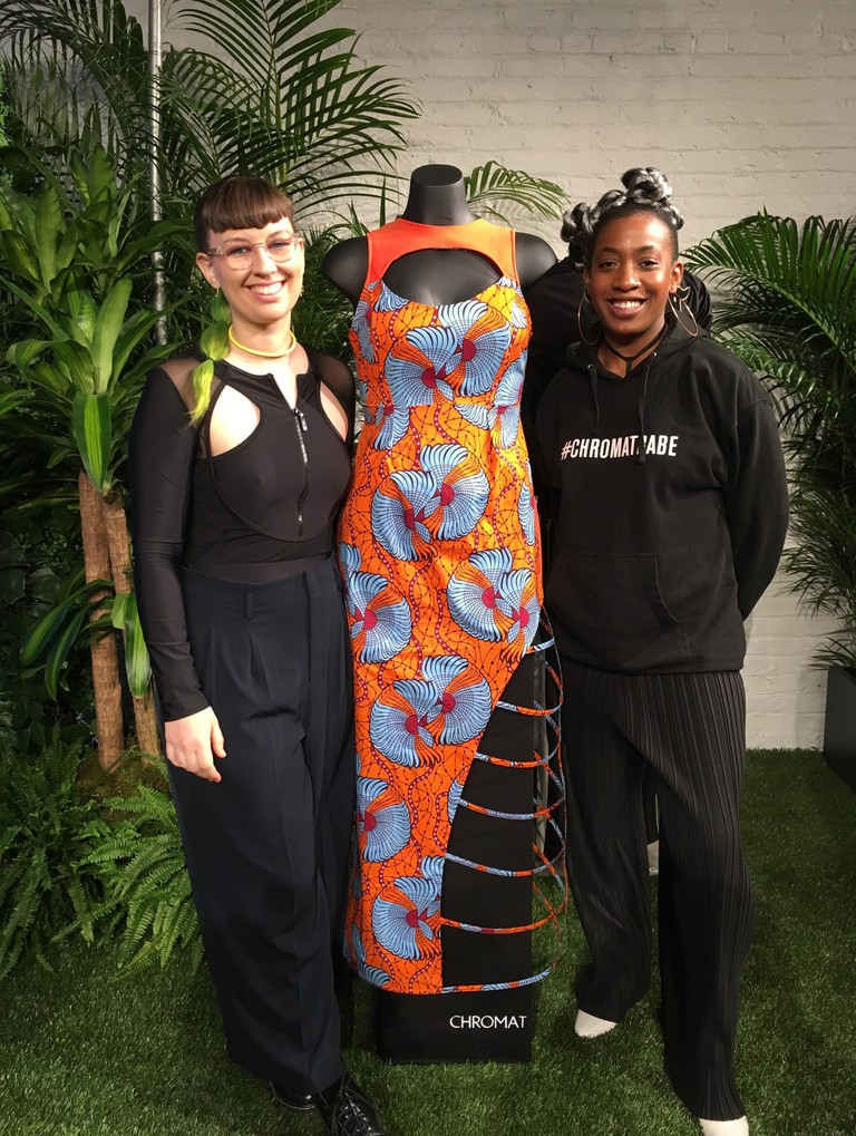 "Becca McCharen-Tran, left, the founder of Chromat, stands with Chromat designer Tolu Aremu and a dress they created for a small collection inspired by the film ""Black Panther,"" in New York."