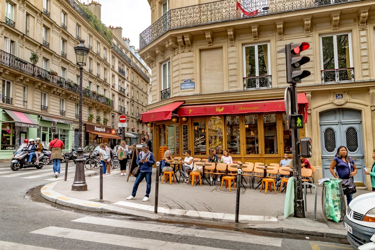 A woman looks at her mobile phone standing outside Le Ventura restaurant cafe on Rue des Martyrs in Monmartre in the 9th arrondissement of Paris
