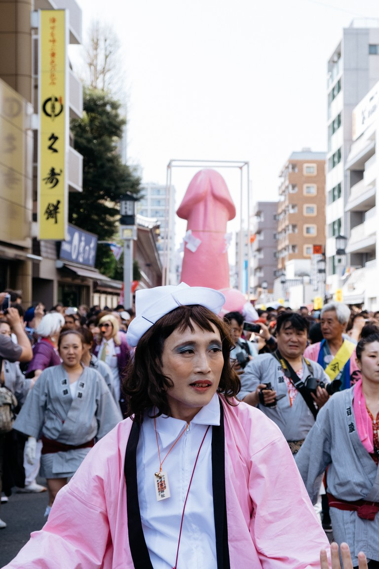 Many people and the Elizabeth Mikoshi make their way down the street