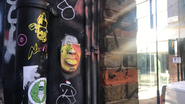 One of many plaster cast faces from street artist Gregos, attached to the back wall of The Old Blue Last pub in Shoreditch